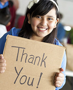 Child holding a sign that says Thank You!